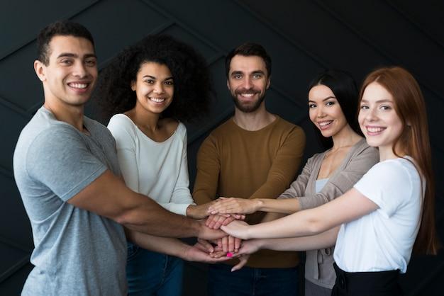 Vista frontale gruppo di giovani che tengono le mani