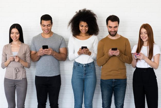Vista frontale gruppo di persone che mandano sms sui loro telefoni cellulari