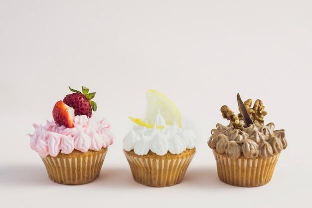 Vista frontale gustosi cupcakes di sapori diversi