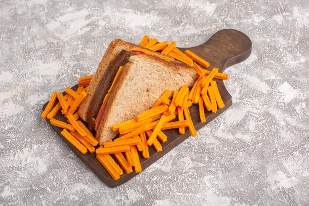 Vista frontale gustoso pane tostato con prosciutto formaggio e patatine fritte su bianco