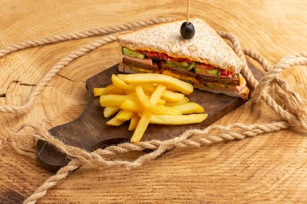 Vista frontale gustoso panino con prosciutto di oliva pomodori verdure insieme a corde di patatine fritte su legno