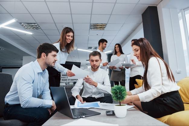 Vista frontale. il gruppo di giovani liberi professionisti nell'ufficio ha conversazione e sorridere