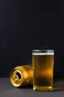 Vista frontale lattina di birra accanto al bicchiere con la birra