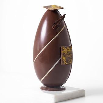 Vista frontale lungo uovo di cioccolato disegnato con linee bianche sulla scrivania bianca