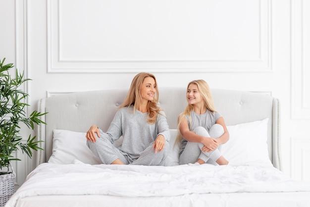 Vista frontale madre e figlia, seduto nel letto