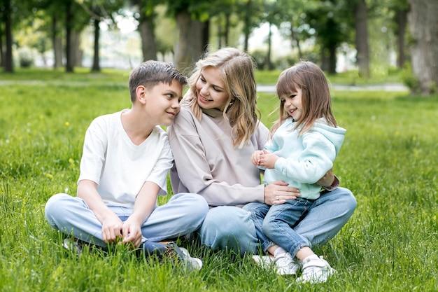 Vista frontale mamma e bambini seduti sull'erba