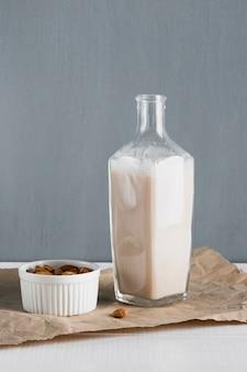 Vista frontale mandorle con bottiglia di latte di mandorle