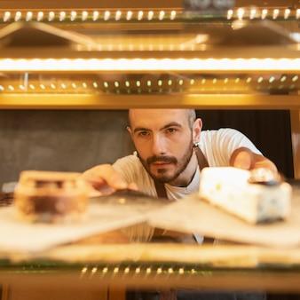 Vista frontale maschio che controlla i prodotti della caffetteria