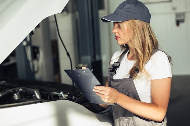 Vista frontale meccanico femminile auto ispezionando
