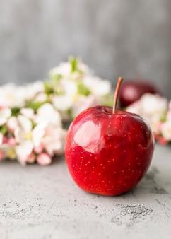 Vista frontale mela e fiori sfocati