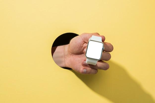 Vista frontale mockup smartwatch tenuto da persona