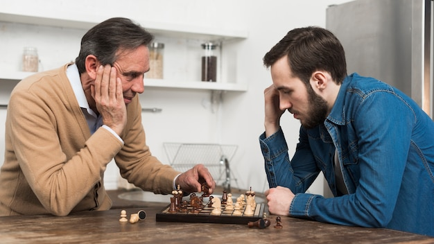 Vista frontale padre e figlio, giocare a scacchi in kithcen