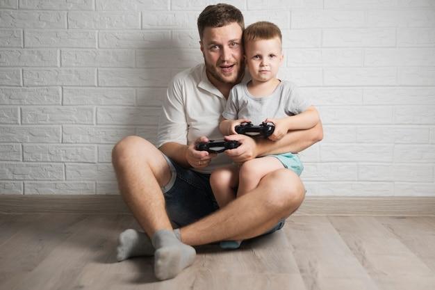 Vista frontale padre e figlio, giocare ai videogiochi