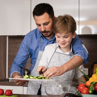 Vista frontale padre insegnamento figlio a tagliare le verdure
