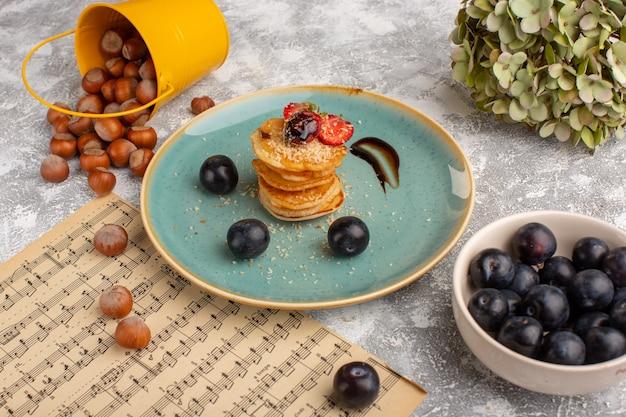 Vista frontale patatine salate progettate con fragole all'interno del piatto insieme a prugnoli sul tavolo bianco, frutti di bosco snack patatine fritte