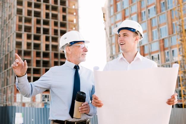 Vista frontale persone con progetto di costruzione e caffè