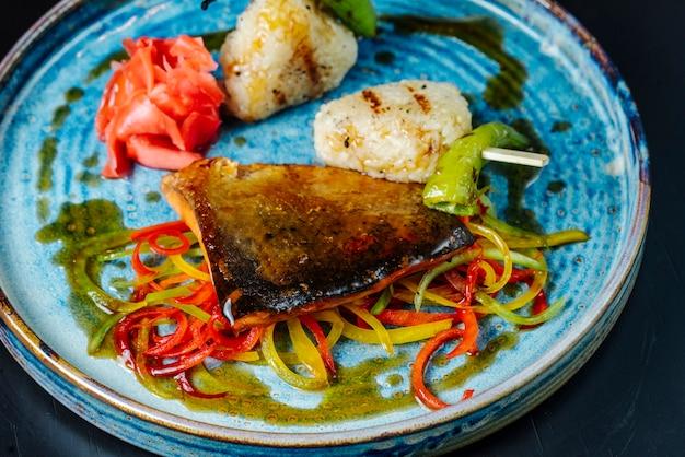 Vista frontale pesce alla griglia con salsa e peperone dolce su un piatto