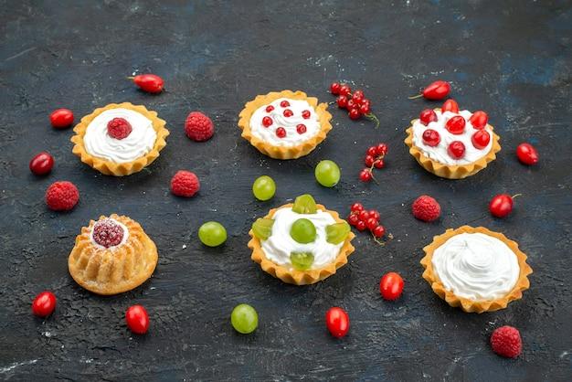 Vista frontale piccole torte deliziose con crema e frutta fresca sul biscotto di biscotti alla frutta scrivania scura
