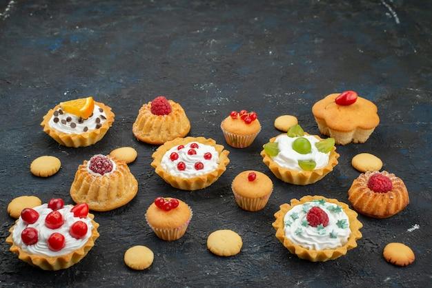 Vista frontale piccole torte deliziose con panna e frutta fresca sullo zucchero della torta biscotti dolci scuro scrivania