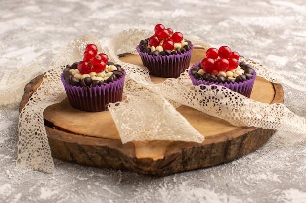 Vista frontale piccoli brownies al cioccolato con mirtilli rossi su grigio