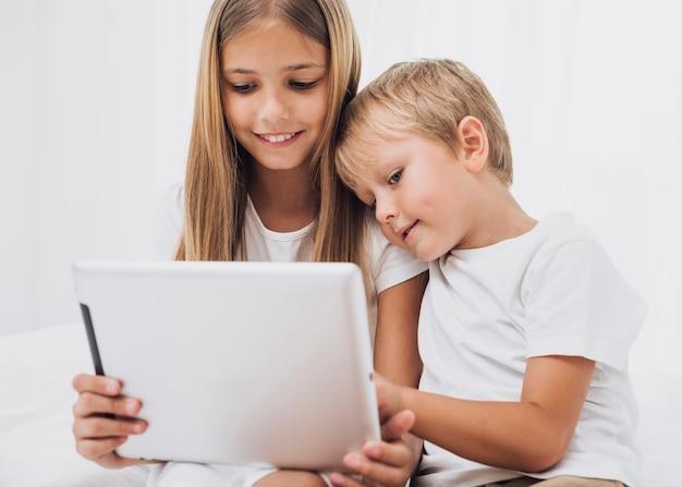 Vista frontale piccoli fratelli stare a letto mentre guardando il loro tablet