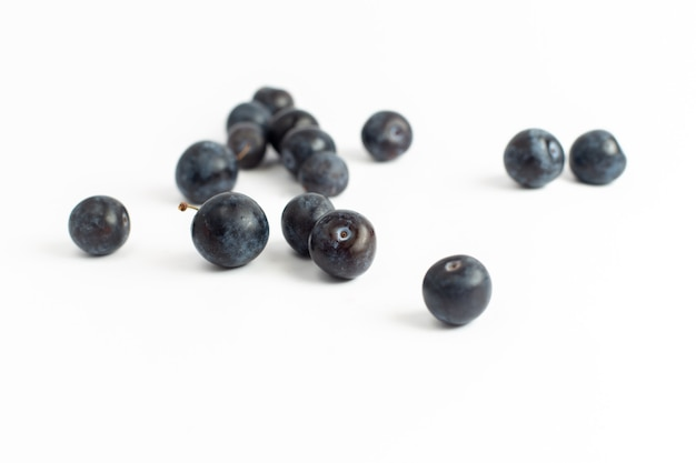 Vista frontale prugnoli freschi frutti aspri e scuri sullo sfondo bianco frutta fresca estate succo di vino