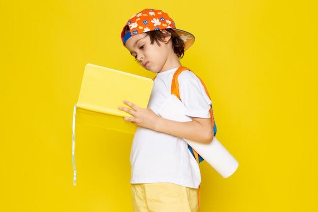 Vista frontale ragazzino in t-shirt bianca lettura quaderno sul pavimento giallo