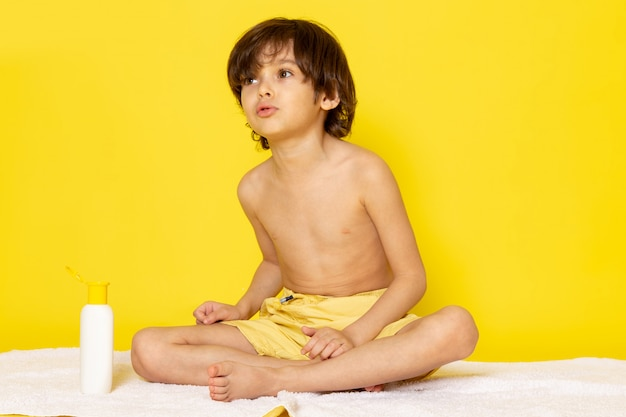 Vista frontale ragazzo adorabile dolce adorabile sull'asciugamano bianco e sulla scrivania gialla