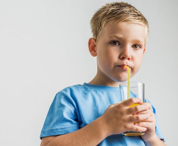 Vista frontale ragazzo carino bere succo
