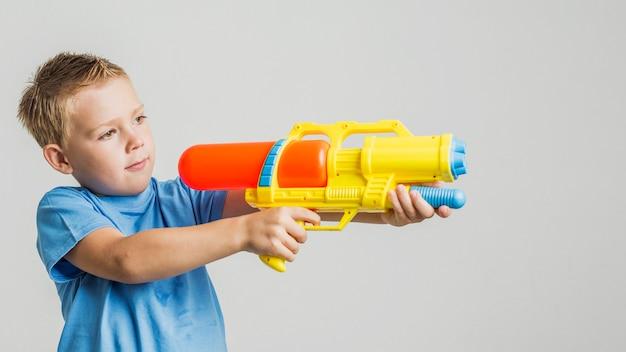 Vista frontale ragazzo carino con pistola ad acqua