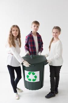 Vista frontale simpatici bambini piccoli felici di riciclare