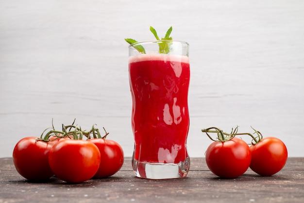 Vista frontale succo di pomodoro fresco con foglia insieme a pomodori interi su grigio, frutta verdura cocktail di colore