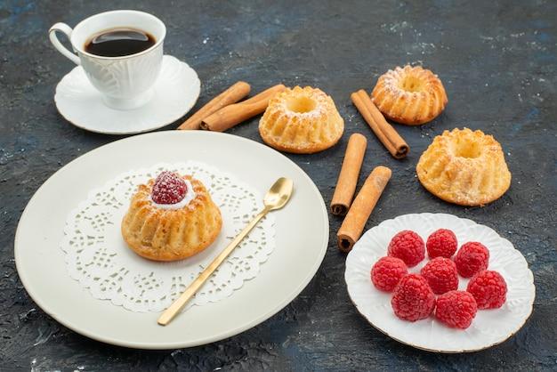 Vista frontale tazza di caffè con biscotti torta cannella e lamponi freschi sulla superficie scura dolce