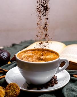 Vista frontale tazza di cappuccino con biscotti e un libro sul tavolo