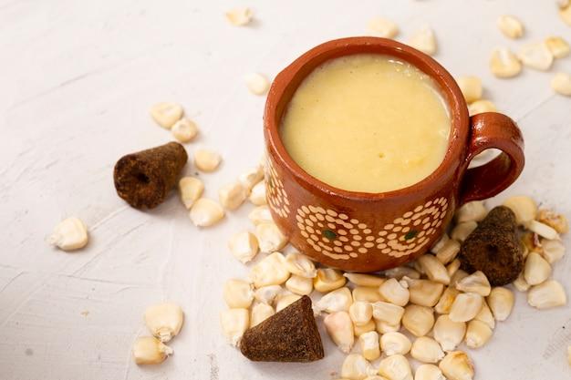 Vista frontale tazza di zuppa e chicchi di mais