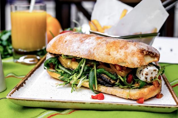 Vista frontale toast con verdure e salsa al pesto con patatine fritte e succo d'arancia