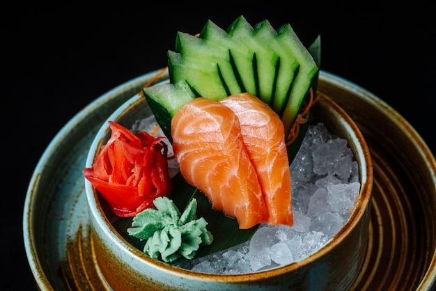 Vista frontale tritato pesce rosso affumicato con wasabi tritato cetriolo e zenzero nel ghiaccio