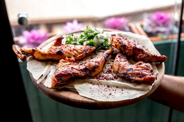 Vista frontale un uomo tiene un vassoio con cosce di pollo alla griglia su una pita con cipolle ed erbe
