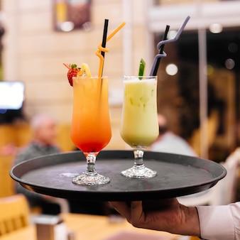 Vista frontale un uomo tiene un vassoio con due cocktail