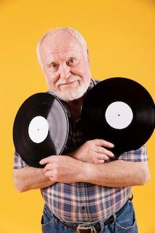 Vista frontale uomo anziano con dischi musicali