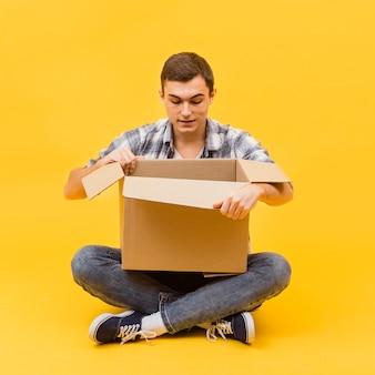Vista frontale uomo che apre il pacchetto consegnato