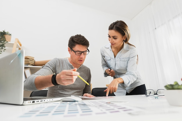 Vista frontale uomo e donna che lavora su documenti aziendali