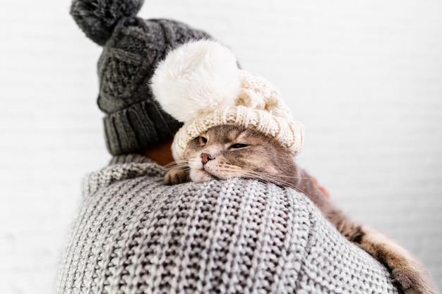 Vista frontale uomo e gatto che indossano entrambi il cappello di pelliccia