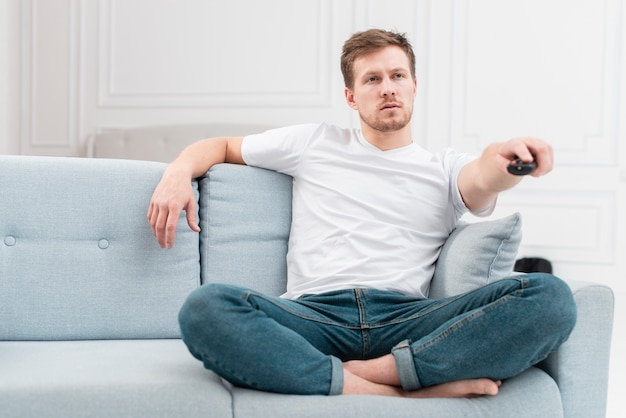 Vista frontale uomo usando il telecomando per cambiare canale