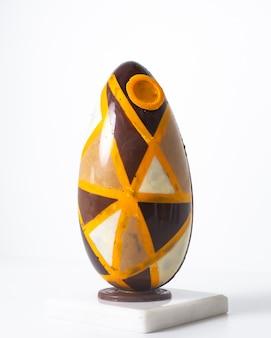 Vista frontale uovo colorato progettato sul pavimento bianco