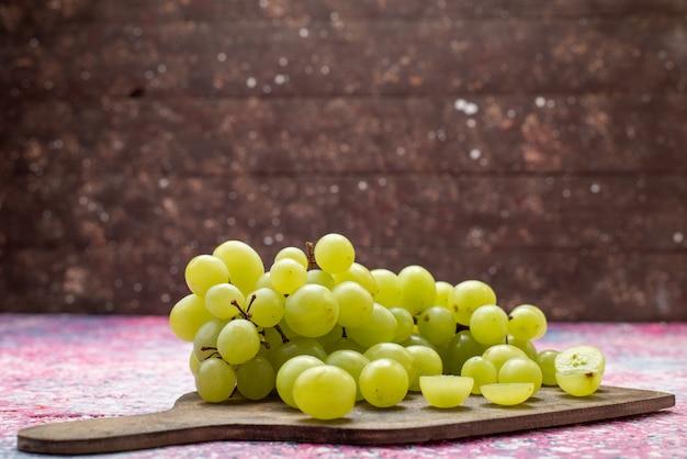Vista frontale uva verde fresca frutta pastosa e succosa sulla superficie luminosa frutta morbida e succosa viola
