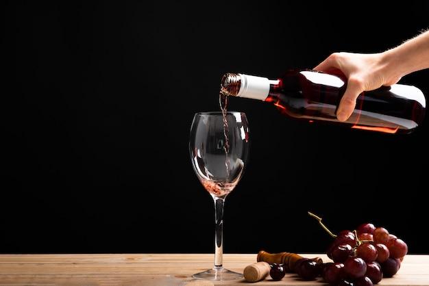 Vista frontale vino rosso versato in un bicchiere