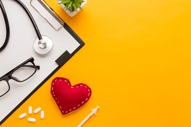 Vista in elevazione degli occhiali; tavoletta; iniezione; a forma di cuore cucito; pianta succulenta; stetoscopio su sfondo giallo