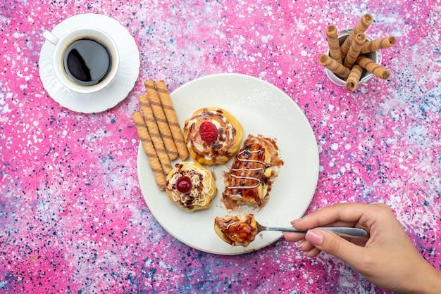 Vista in lontananza deliziose torte fruttate con crema e cioccolato all'interno del piatto bianco insieme al caffè sul pavimento rosa torta biscotto dolce cuocere