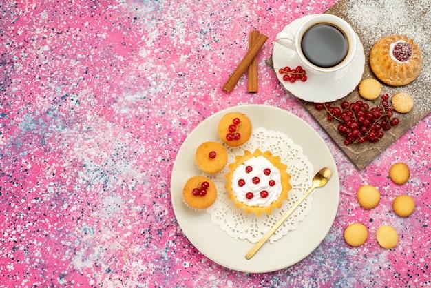 Vista in lontananza piccola torta con biscotti alla crema mirtilli freschi insieme a una tazza di caffè e cannella sul biscotto di superficie colorata